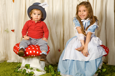 Little mad hatter and Alice in Wonderland sitting on toadstools