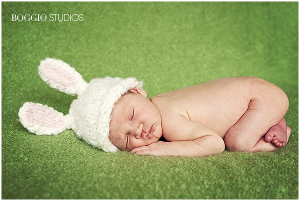 newborn baby lying naked with bunny hat