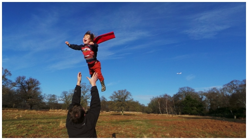 Boy dressed as Superman being thrown in the air by father