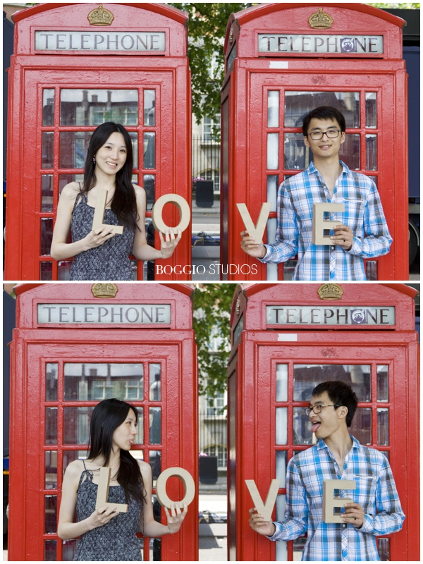 Couple stood in front of red phone boxes