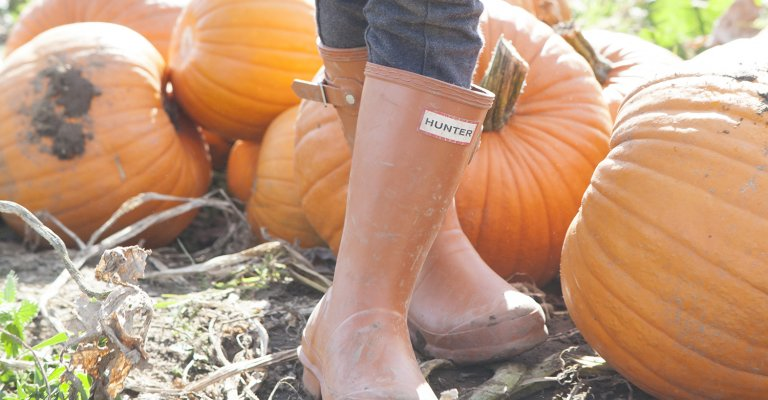 Orange hunter wellies with pumpkins in background