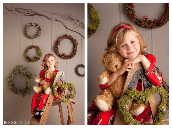 girl holding teddy bear in front of Christmas theme wall