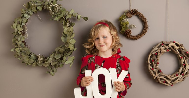 girl holding joy letters in front of wreathes