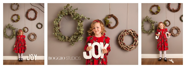 GIrl holding JOY Letters in front of wreaths