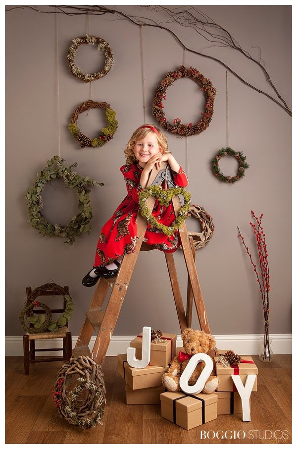 girl sitting on ladder in front of christmas wreathes