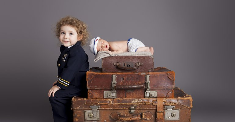 newborn on vintage suitcase with older brother