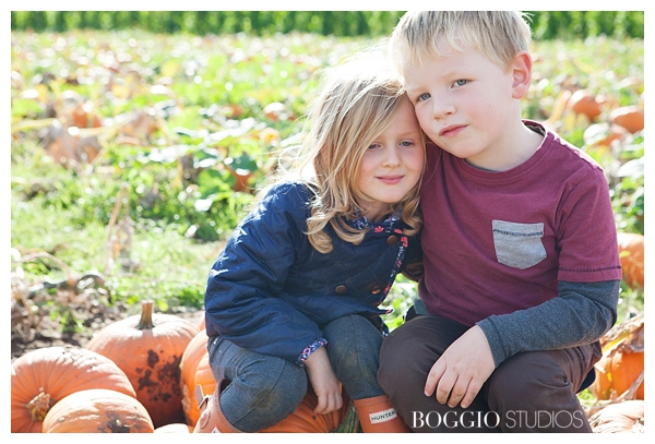 boy and girl, aged 5, sitting in pumpkin patch