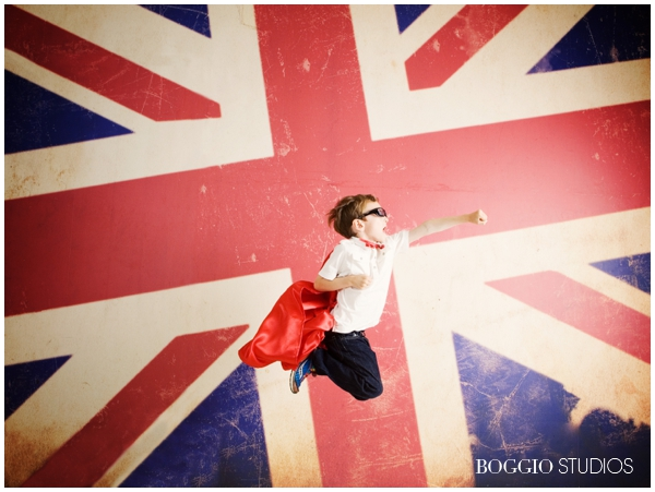 little boy flying in the air like superman on a union flag background
